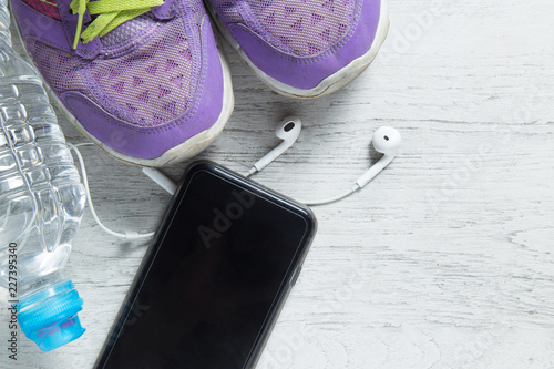 Poster Sport flat lay purple shoes, smartphone and workout equipments on white wooden background with copyspace for your text. Concept healthy lifestyle and diet.
