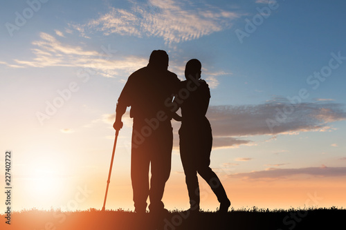 Silhouette Of Woman Assisting Her Disabled Father