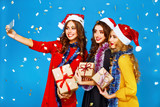 portrait of three happy young women in santa claus hat with gift make selfie .Christmas concept. in evening dresses on party over blue background. firecrackers in the background