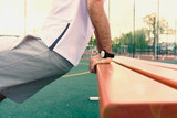 a young guy with a beard in a white sports shirt is engaged in physical training to strengthen muscles and health on an outdoor playground on a hot summer day