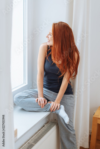 Foto Murales Casual relaxed woman sitting on a window seat