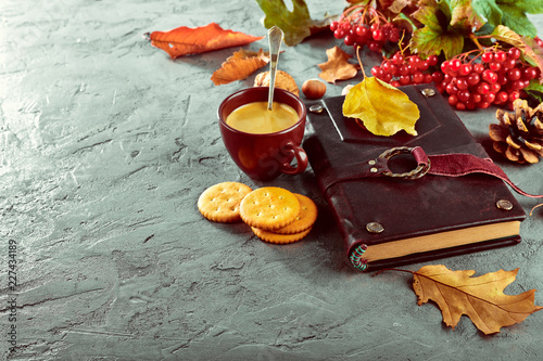 Wall mural Hot coffee and book with yellow leaves branch viburnum
