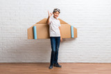 Boy playing with cardboard airplane wings on his back showing an ok sign with fingers