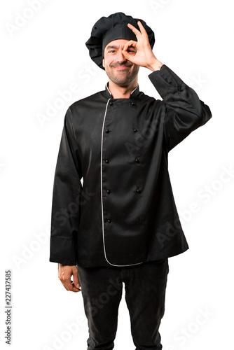 Szef kuchni mężczyzna W czarnym mundurze robi śmiesznej i szalonej twarzy emocji na odosobnionym białym tle
