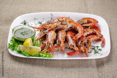 Fototapeta Grilled shrimps with dill sauce and lemon on a white plate