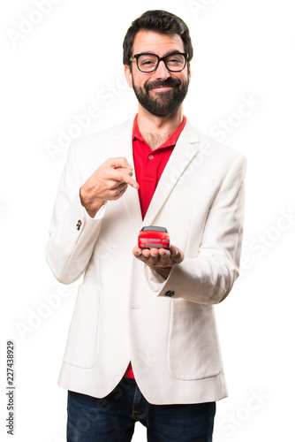 Leinwandbild Motiv Happy Brunette man with glasses holding little car on white background