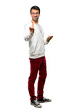Full body of Man with glasses and listening music showing and lifting a finger in sign of the best on white background - 227441171