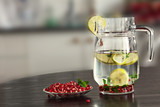 Pitcher with lemon and mint water and pomegranate seeds.