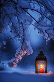 Candle lantern under the snowy branches at dusk. Christmas time in a wintery garden. - 227444582