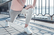 Quadro It is ok. Bridge estranging on background, female person touching knee while training