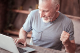Having fun. Close up elderly man expressing cheer while using a laptop and showing a hand clenched in fist - 227451770
