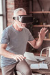 New reality. Portrait of elderly man touching the air while wearing virtual mask and expressing interest