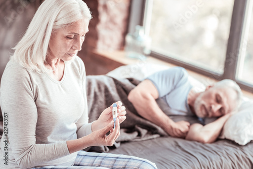 Leinwandbild Motiv Health problems. Portrait of elderly woman looking at thermometer with sadness while her husband sleeping in bed