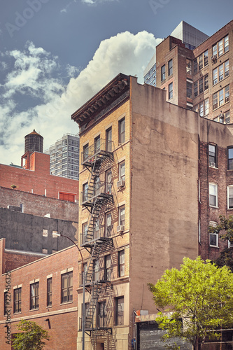 Foto Murales Old building with fire escape in downtown New York, color toned picture, USA.