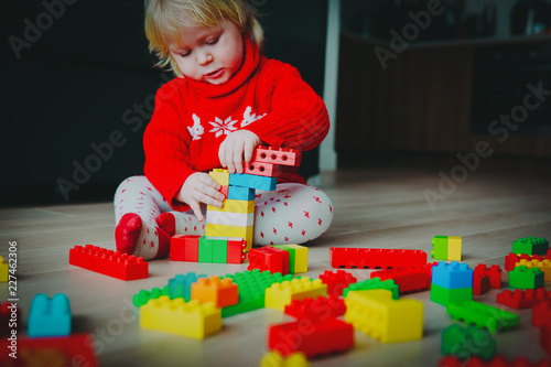 little baby playing with colorful plastic blocks at home