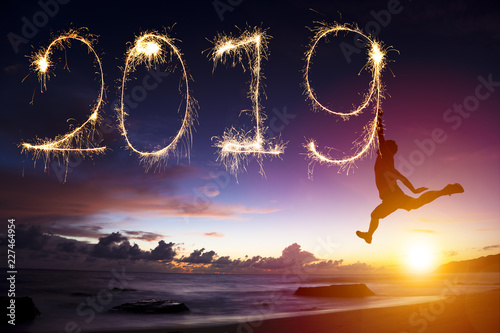 Foto Murales happy new year 2019. man jumping and drawing on beach