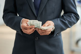 Close-up of businessman in black suit counting dollar currencies - 227473796