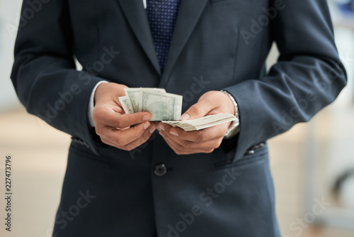 Fridge magnet Close-up of businessman in black suit counting dollar currencies
