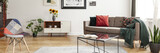 Horizontal photo of a living room interior with a sofa, table, sunflowers and patterned chair. Real photo - 227481144