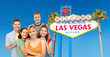 travel, tourism and vacation concept - group of happy smiling friends over welcome to fabulous las vegas sign background