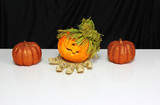 Isolated Halloween orange pumpkins and skeleton wrist. Black and white background. Copy space for text.