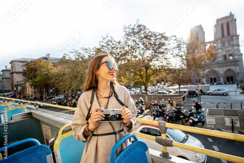 Young woman enjoying a beautiful view on the Notre-Dame cathedral during a bus tour in Paris, France - 227489566