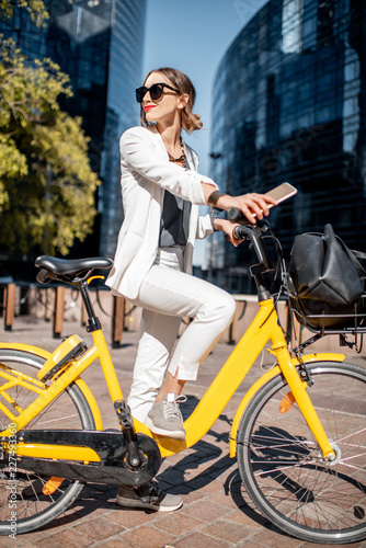 Sticker Portrait of a stylish business woman in white suit standing with bicycle at the financial district with modern buildings on the background