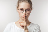 Cute mysterious girl wearing eyeglasses in casual outfit showing silence sign holding forefinger on lips, or having a big secret isolated on white background - 227503175