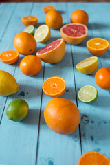 Tropical citrus fruits, whole and sliced oranges and lemons of different colours on blue wooden background. Selective focus