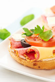 Sandwiches with salami, cream cheese, tomatoes, camembert, black olives, fresh parsley and basil served on a plate. Home made food Symbolic image Concept for a tasty and healthy meal White background  - 227506187