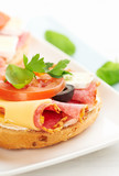 Sandwiches with salami, cream cheese, tomatoes, camembert, black olives, fresh parsley and basil served on a plate. Home made food Symbolic image Concept for a tasty and healthy meal White background  - 227506316