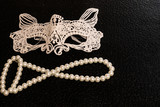 Openwork, white, carnival mask of starched fabric for a costume for a ball or Halloween. White round pearls, beads. Original holiday decorations