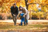 Young family having fun in the autumn park with his son. - 227529784