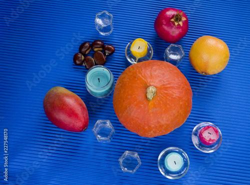 nature morte, décoration de motif d'automne - citrouille, châtaignes, mangue, grenade et pamplemousse sur fond bleu - 227548170