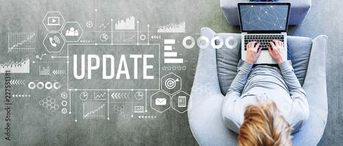 Leinwandbild Motiv Update with man using a laptop in a modern gray chair