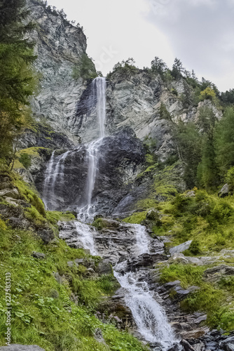 Waterfall in the forest in Austria near Heiligenblut am Großglockner - 227583313