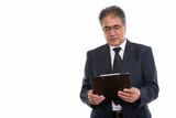 Studio shot of senior Persian businessman reading on clipboard - 227588963