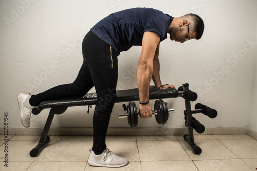 Poster Man exercising with dumbbells, exercising back on bench