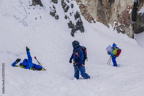 Off-piste skiers are practicing rock climbing.