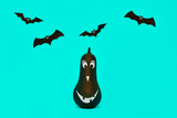 Cute Halloween pumpkin with funny smiling face and paper bats flying over pastel blue background. Halloween concept. - 227601375