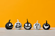 Cute Little Black and White Halloween Pumpkins with funny facial expressions standing side by side on white wooden table over orange background. Halloween concept.