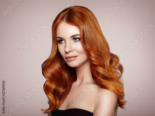 Leinwanddruck Bild Redhead Girl with Long Healthy and Shiny Curly Hair. Care and Beauty. Beautiful Model Woman with Wavy Hairstyle. Make-Up and Black Dress