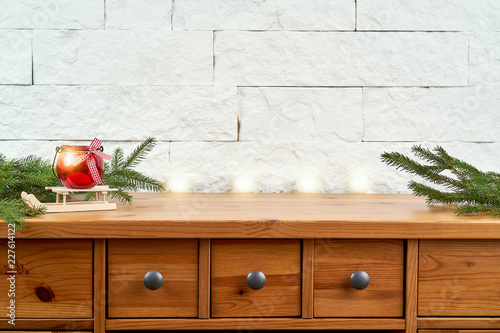 Christmas decoration with twigs of spruce and a red lantern on an old shelf on the background of a white brick wall - 227614122