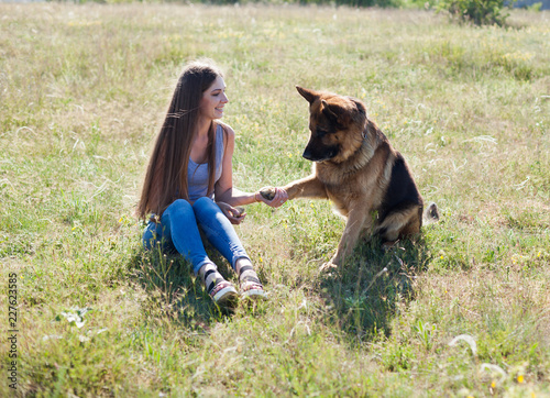 Leinwanddruck Bild woman plays with the dog German Shepherd when training
