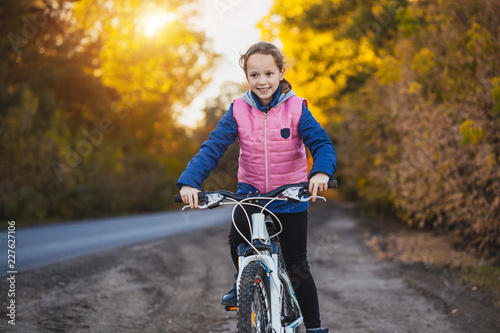 Foto Murales girl on a bicycle in the sunny autumn forest. girl cycling outdoors