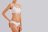 Slim body of a young woman in lingerie on a gray background. - 227628745