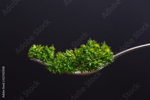 Foto Murales Fork with leaf of parsley on isolated on black. Macro. Diet concept