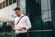 Entrepreneur standing on street checking mobile phone