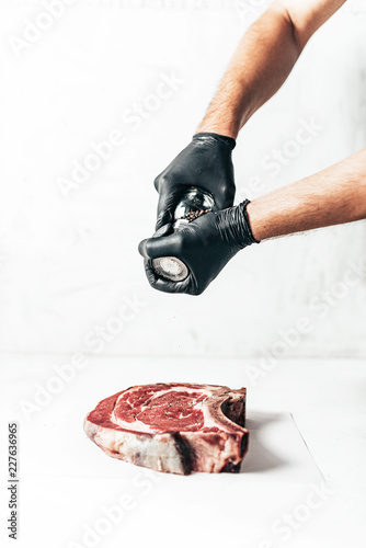 Chef sprinkles pepper on raw meat steak on white background.