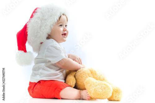 Leinwanddruck Bild Happy baby boy with a Santa hat with a Christmas present box
